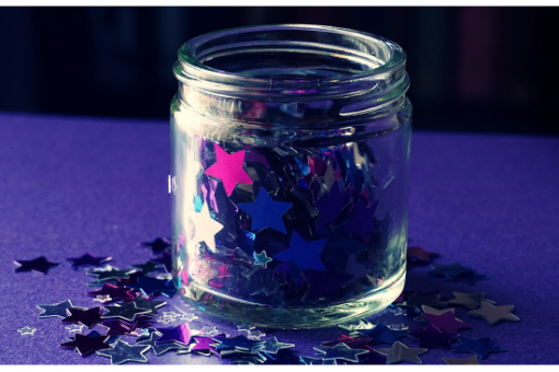 pink and blue stars in and around a glass jar with